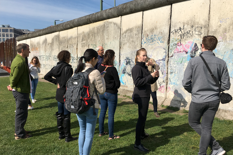Students stand near the remnants of the Berlin Wall.