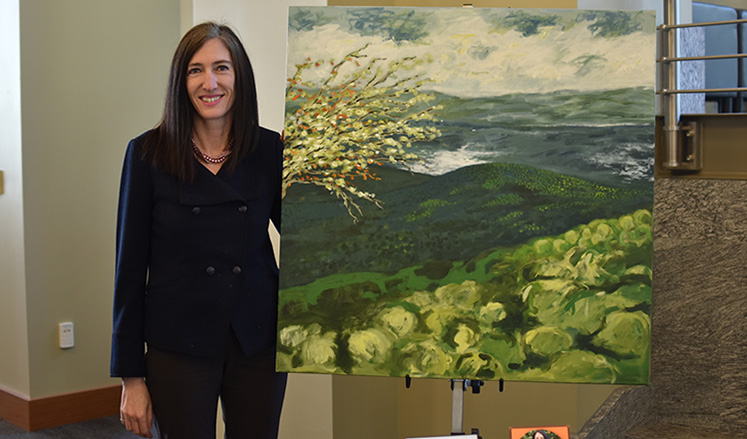 Catherine Chastain-Elliott, senior associate dean of academic affairs, with My Father Sees, her original oil painting.