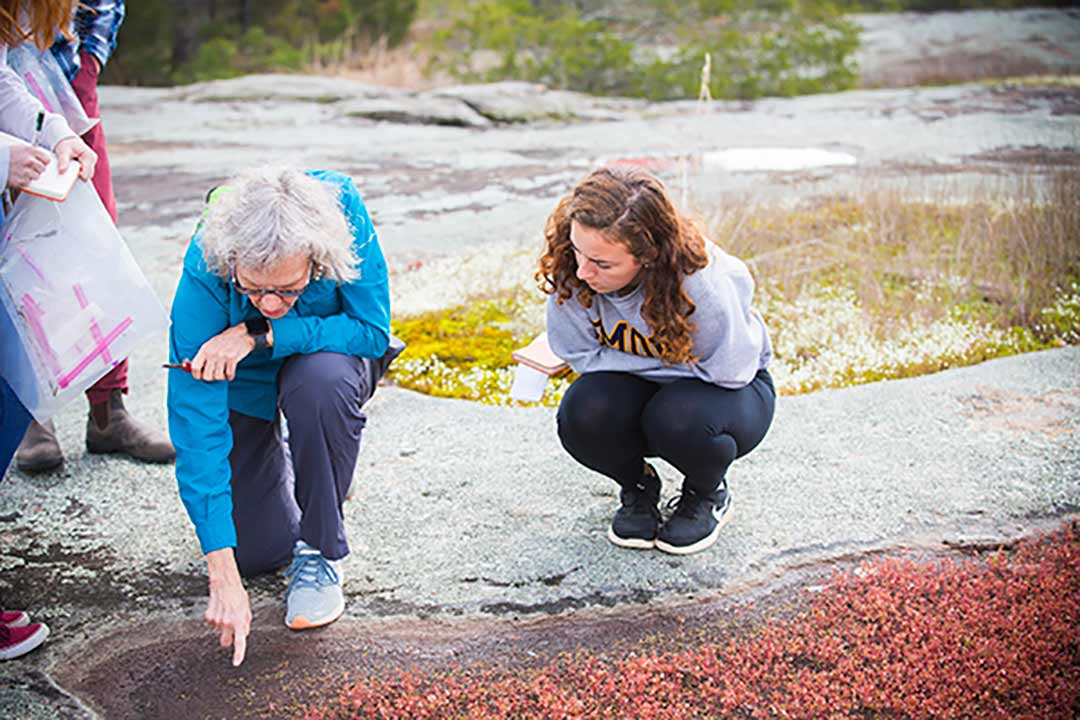 Eloise Carter and a student examine nature samples at a local mountain.
